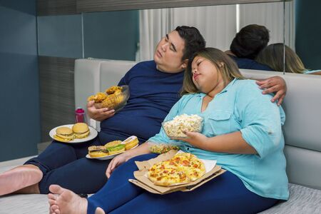 Fat Asian couple falling asleep, while watching television with junk foods scattered around them in their bedroom
