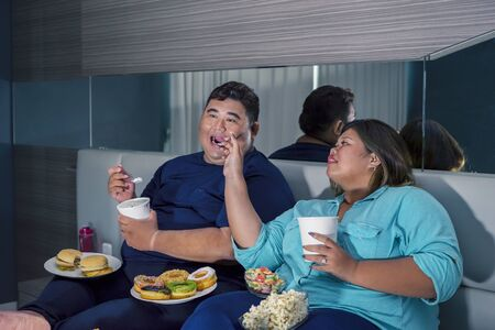 Portrait of fat Asian couple eating ice cream romantically, while watching television with other junk foods scattered around them in their bedroom Zdjęcie Seryjne