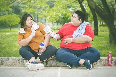 Fat Asian man offering a bottle of water to his fat female friend, while taking a break after working out on the pavements at the park