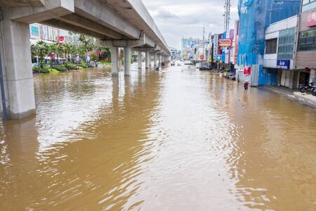 JAKARTA, Indonesia - January 13, 2020: Flooded road with pedestrians sheltering in nearby stores at Jakarta city