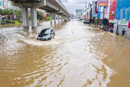 JAKARTA, Indonesia - January 13, 2020: Flooded road with car crossing the flood and pedestrians nearby sheltering in some district at Jakarta city