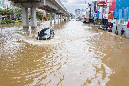 YAKARTA, Indonesia - 13 de enero de 2020: Carretera inundada con un automóvil que cruza la inundación y peatones cercanos que se refugian en algún distrito de la ciudad de Yakarta