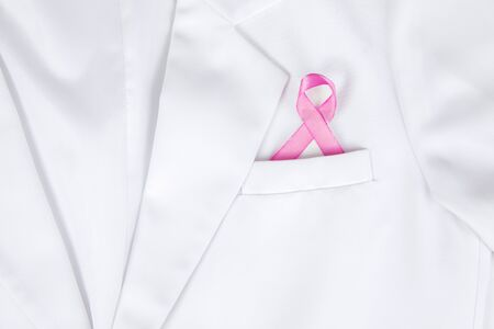 Closeup of a pink ribbon inserted to lab coats pocket, isolated in white lab coat background