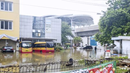 JAKARTA, Indonesia - January 13, 2020: Flooded office buildings and buses with a man standing in the middle of it at Jakarta city Stok Fotoğraf