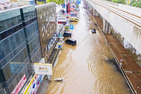 JAKARTA, Indonesia - January 13, 2020: Aerial view of citizens crossing the flood underneath railways in some district at Jakarta city