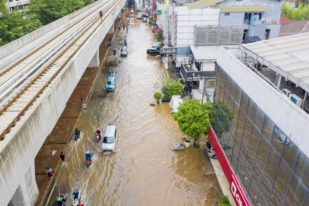 JAKARTA, Indonesia - January 13, 2020: Aerial view of vehicles crossing the flood underneath railways in some district at Jakarta city