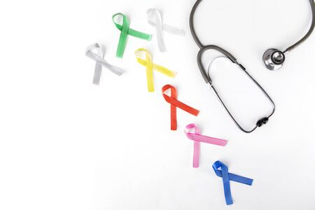 Flat layout of colorful ribbons beside a stethoscope, isolated in white background