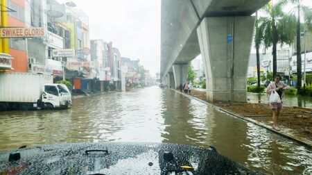 JAKARTA, Indonesia - January 13, 2020: Car view of flooded road with pedestrians nearby in some district at Jakarta city