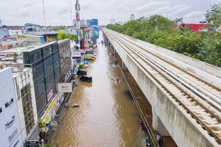 YAKARTA, Indonesia - 13 de enero de 2020: Vista aérea de motocicletas que cruzan la inundación debajo de los ferrocarriles en algún distrito de la ciudad de Yakarta