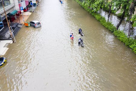 JAKARTA, Indonesia - January 13, 2020: Aerial view of motorcycles crossing the flood in some residence at Jakarta city