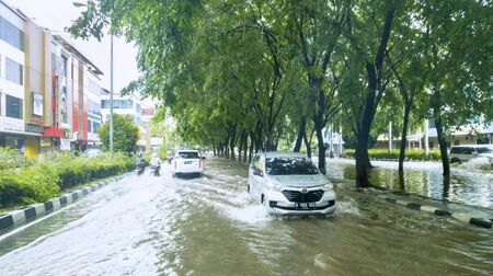 JAKARTA, Indonesia - January 13, 2020: Vehicles crossing high flood on the residence road in somewhere at Jakarta city