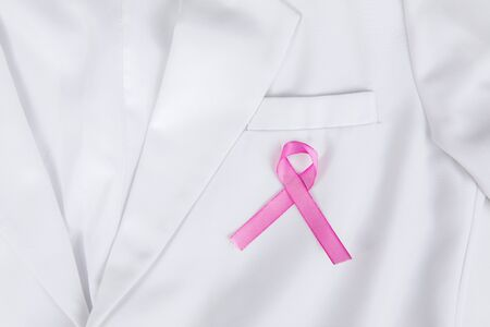 Closeup of a pink ribbon attached to lab coats pocket, isolated in white lab coat background