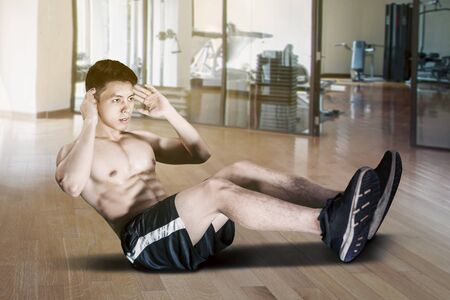 Portrait of young Asian man doing workout and sit up in the gym. Healthy lifestyle concept