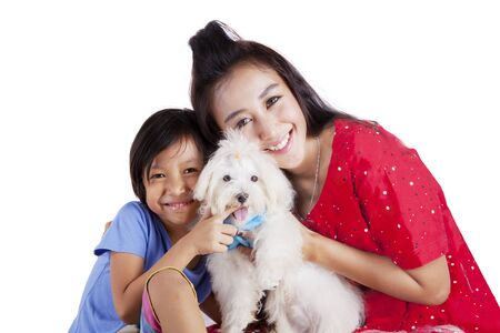 Happy little girl and her mother hugging a maltese dog in the studio, isolated on white background
