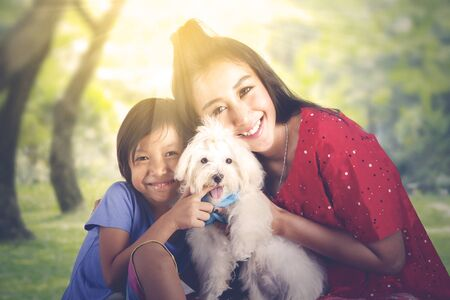 Happy young woman and her daughter hugging a maltese dog while smiling at the camera in park