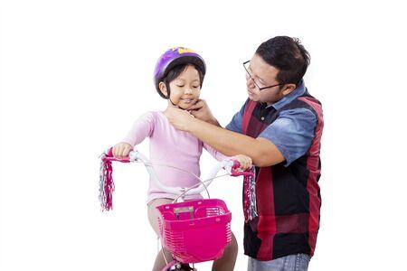 Ritratto di un bell'uomo asiatico che mette con cura un casco da bici per sua figlia mentre si inginocchia, isolato in uno sfondo bianco