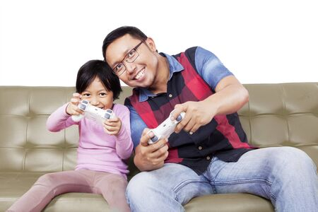 Portrait of handsome Asian man playing video games enthusiastically with his daughter, isolated in white background