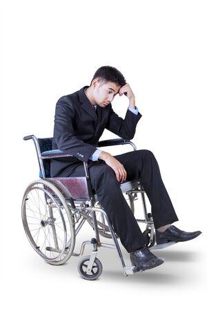 Retrato de frustrado joven empresario sentado en la silla de ruedas, aislado sobre fondo blanco. Foto de archivo