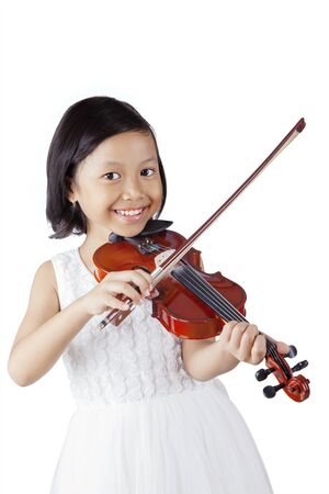 Porträt eines glücklichen kleinen Mädchens, das Geige spielt, während es im Studio in die Kamera lächelt, isoliert auf weißem Hintergrund
