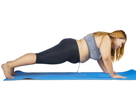 Side view of obese woman exercising by doing push up on the mat, isolated on white background Stock Photo