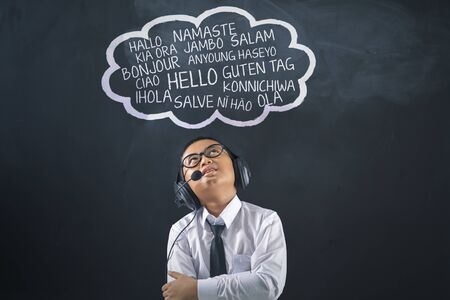 Boy with headphones and greeting words in different language on speech bubble. Learn Foreign Language concept Reklamní fotografie
