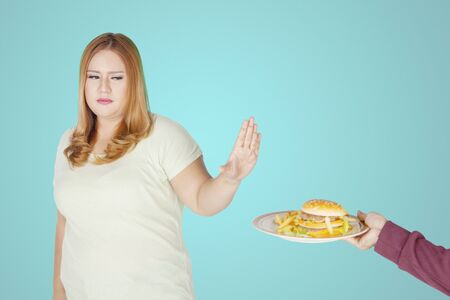 Portrait of overweight woman refusing to eat junk food in the studio. Healthy lifestyle concept