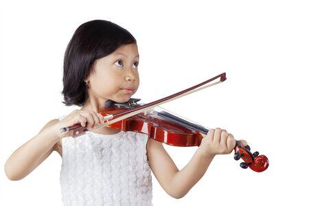 Portret dziewczynki uczy się grać na skrzypcach w studio, na białym tle