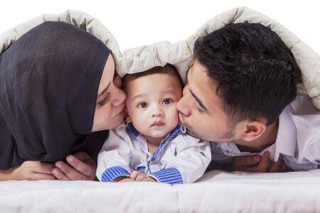 Portret szczęśliwych młodych rodziców całujących swoje dziecko pod kocem na łóżku Zdjęcie Seryjne