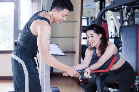 Entrenador personal joven ayudando a la mujer joven a hacer ejercicio en equipos de gimnasia en el gimnasio Foto de archivo
