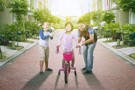 Asian father & son cheering & clapping for the girl which succeeded riding a bicycle while smiling at camera on the residence road at sunny day