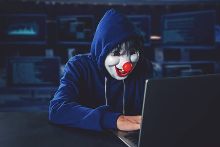 Hacker wearing clown mask hacking on a laptop computer with computer monitors background