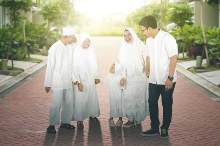 Happy multi-generation muslim family walking together at park