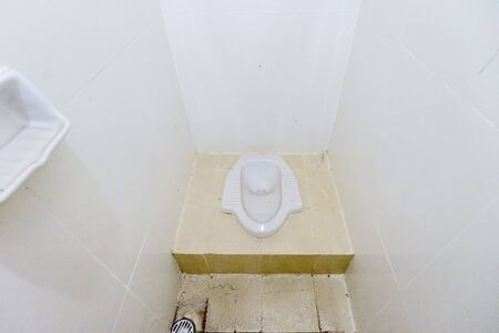 Top down view of a dirty squat toilet in an empty modern house in Asian country Stock Photo