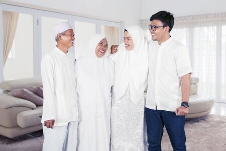 Happy muslim family portrait with parents, son and daughter laughing together at home