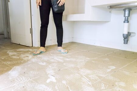 Woman stands on dirty floor of an empty house