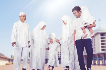 Happy multi-generation muslim family walk together in front of a mosque