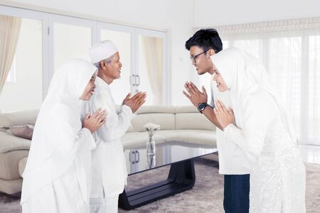 Son and daughter greetings their parents during Eid al-fitr celebration at home