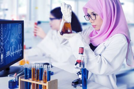 Portrait of beautiful scientist doing experiment with chemical liquid in laboratory