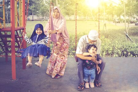 Elderly Asian muslim grandparents playing with their grandchildren, while swinging in the playground at the park