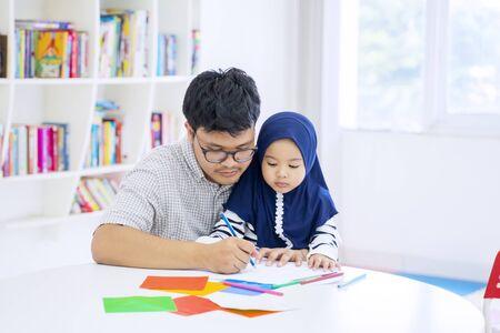 Porträt eines gutaussehenden asiatischen Mannes, der seiner entzückenden muslimischen Tochter beibringt, wie man in einem Klassenzimmer zeichnet