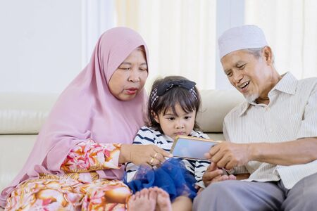 Portrait of elderly Asian muslim parents sitting on a couch, while accompanying their granddaughter playing games at her phone in the living room