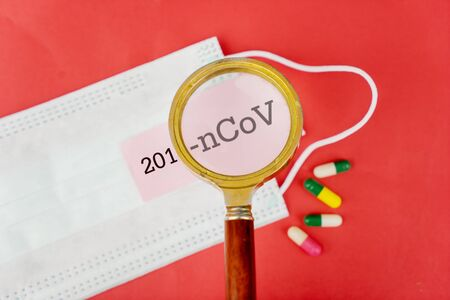 Closeup of a magnifying glass zooming in to the 2019 nCoV label on a face mask and capsules, isolated in red cardboard background Stok Fotoğraf