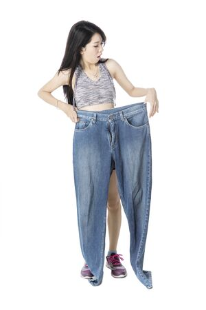 Shocked woman shows her weight loss success by holding an old jeans in the studio, isolated on white background