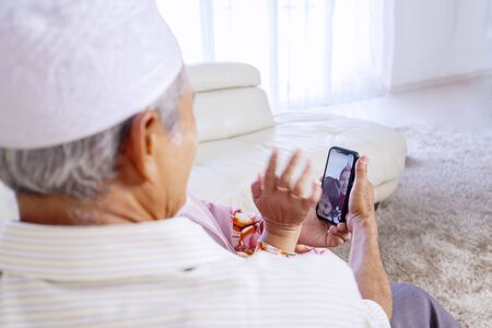 Elderly Asian muslim couple waving at their daughter & granddaughter while video calling them in their living room