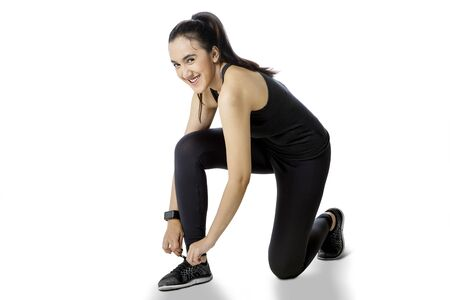 Beautiful young woman in sportswear smiling at the camera while tying shoelaces before exercising in the studio, isolated on white background
