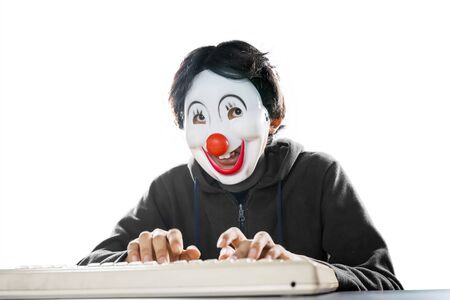 Portrait of unidentified man wearing clown mask while typing on his desktop, isolated in white background