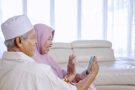 Elderly Asian muslim couple waving at their grandchildren, while video calling them in their living room
