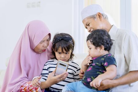 Portrait of senior Asian muslim parents sitting on a couch, while accompanying their grandchildren playing games at her phone in the living room
