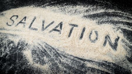 Closeup of SALVATION word written on white sand with black wooden background