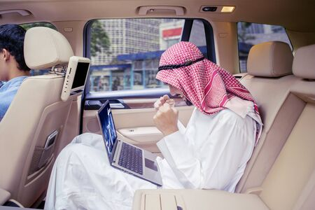 Portrait of Arabian man expressing his success while looking at the financial chart on the laptop screen in the car